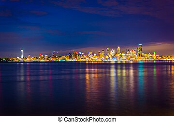 The Seattle skyline and Elliott Bay at night, seen from West...