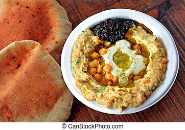 Israeli Hummus with olive oil, herbs, and spices - Hummus...