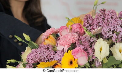 Modern florist makes a bouquet to decorate the hall before...
