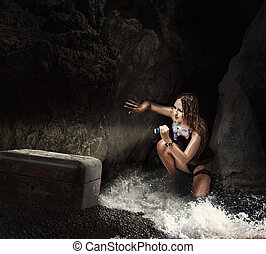 Woman traveler in sea cave with tresure chest - Adventure...