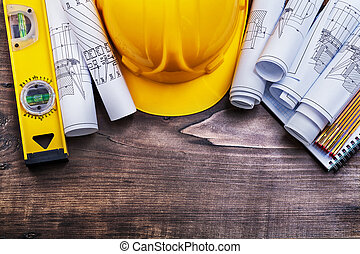 Notepad blueprints hard hat wooden meter and construction level