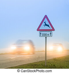 Deer crossing roadsign - Cars passing a traffic sign for...