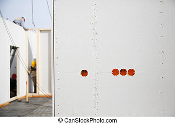 Electricity sockets in a drywall with workers in background...
