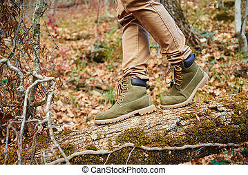 Hiker crossing on fallen tree trunk