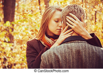 Loving couple in autumn park at sunny day