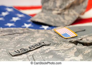 USA army uniform lying over national flag - studio shot - US...