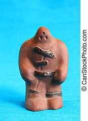 Golem - Small clay figure of golem on blue background