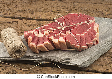 Raw t-bone steak on stone on a wooden table