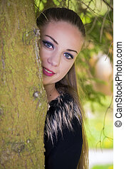 Pretty girl hiding behind the tree