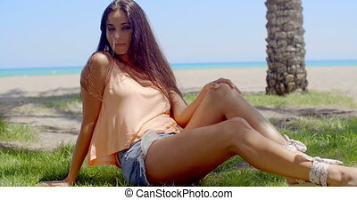 Woman Sitting on Grassy Ground at the Beach - Attractive...