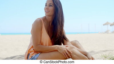 Happy Pretty Woman Sitting at the White Beach Sand