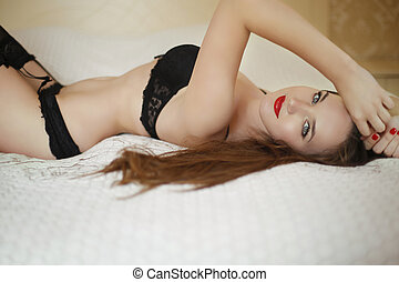 Sensual young beautiful sexy woman in black lingerie lying...