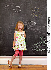 Innocent little girl standing with chalk drawings at home -...