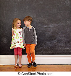 Little boy and girl standing in front of blackboard looking...