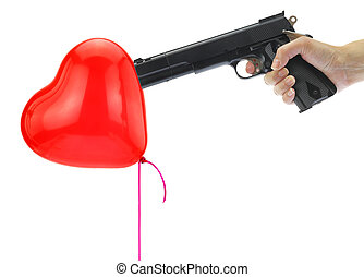 Hand holding at gunpoint a heart balloon isolated on white