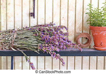 Bunch of sage and pot with herbs in front of an old wall