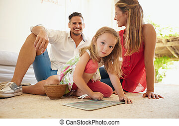 Girl drawing with her parents in living room