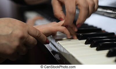 Woman teaches child to play piano - Woman teaches the child...