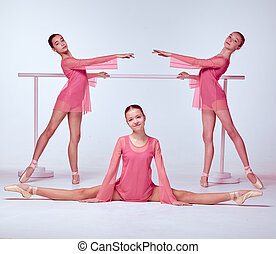 Ballerinas stretching on the bar - Three young ballerinas in...