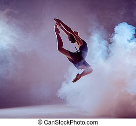 Beautiful young ballet dancer jumping on a lilac background...