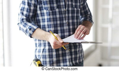close up of man looking and writing to clipboard - repair,...