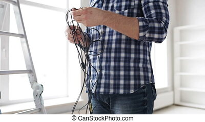 close up of man untangling wires - repair, building,...