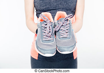 Woman`s hands holding sneakers - Closeup image of a woman`s...