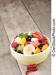 Fresh tasty fruit salad in the bowl on the wooden table