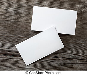 Photo of blank business cards on a dark wooden background....