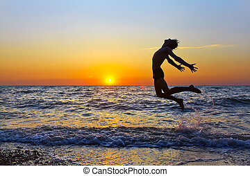 man at sunset - silhouette of a happy man jumping on a...
