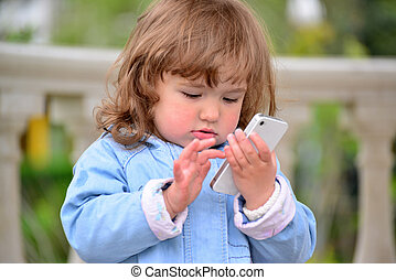Girl two years, with a cell phone in the park - Little girl...