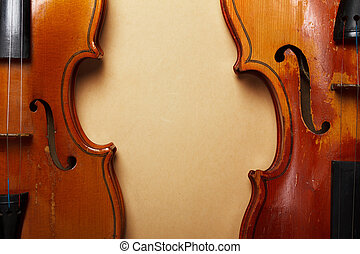 Two grunge old violin on vintage yellowed paper