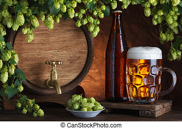Bottled and unbottled beer with barrel and fresh hops for...