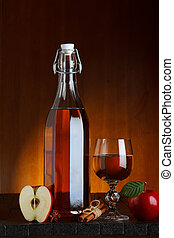 Bottle and glass of apple cider with sliced apple on wooden...
