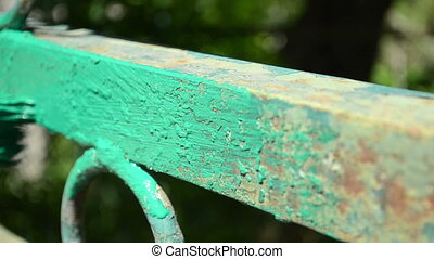 A hand paints metal gate - A hand paints old metal gate in...