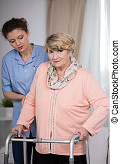 Carer and older woman - Female carer helping older woman...