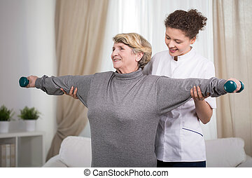 Active older lady exercising arms with dumbbells