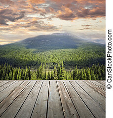 Wooden deck overlooking scenic view of mountains at sunset