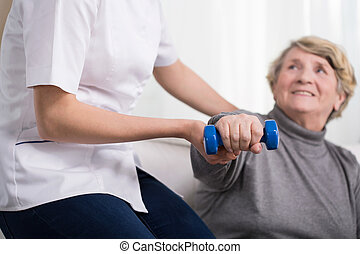 Woman and physiotherapists help - Aged exercising woman and...