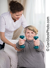 Strong older woman - Strong older active woman lifting the...