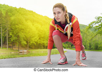 Attractive blonde woman running on track outdoors -...