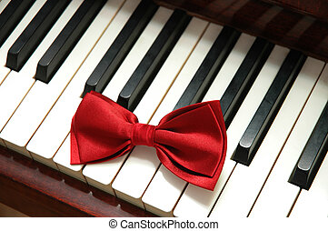 Red bow tie on white piano keys - Red bow tie on white piano...