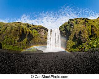 Skogafoss waterfall with rainbow on sunny summer day,...