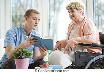 Old woman on a wheelchair - Nurse reading a book with old...