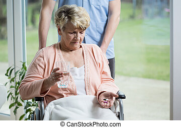 Old woman taking pills - Old woman on a wheelchair taking...