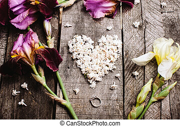 heart shape of white lilac flowers and ring on wood table -...