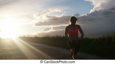 Young lady running on a rural road during sunset