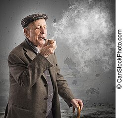 Old man smoking pipe - Old man reflecting while smoking his...