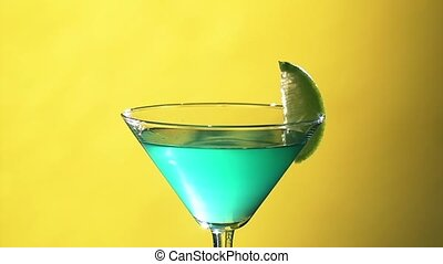 Barman making turquoise cocktail with slice of lime and tubules, close motion, close up, on yellow