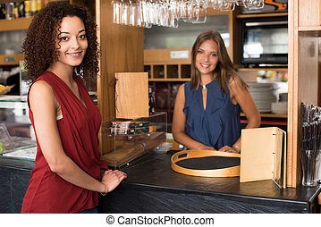 Female baristas - Couple of female baristas standing inside...